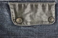 Graues Denimgewebe mit einer Tasche Stockbilder