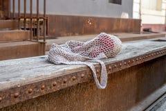Graues Einkaufsnetz mit roten strickenden Schlaufen auf alter hölzerner Bank stockfoto