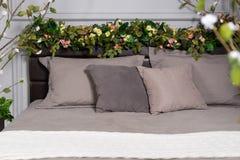 Graues gemütliches Bett mit Blumen auf dem Bettgestell und mit einem weißen Schleier Stockbilder