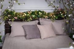 Graues gemütliches Schlafzimmer mit Blumen auf dem Bettgestell Stockbild