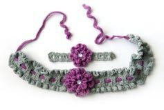 Graues Häkelarbeitstirnband und -armband mit Blumen lizenzfreie stockfotos