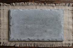 Graues konkretes Schild auf hellem Gewebe und hölzernem braunem Hintergrund lizenzfreie stockfotos