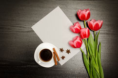 Graues leeres Blatt Papier, rosa Tulpen und einen Becher Kaffee Schwarze Tabelle Stockfoto