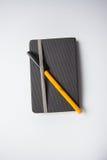 Graues Notizbuch mit einer Orange ballpen auf ihm Lizenzfreie Stockfotos