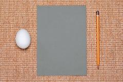 Graues Papier und Bleistift und Ei auf Hintergrund Stockbilder