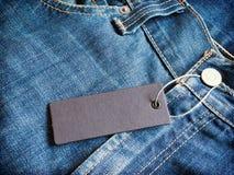 Graues Preismodell des Aufklebers auf Blue Jeans Stockbilder