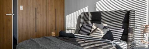 Graues Schlafzimmer mit hölzernem Wandschrank stockbild