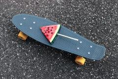 Graues Skateboard der Nahaufnahmemode mit Wassermeloneneis am stiel auf dem Stock Stockfotos
