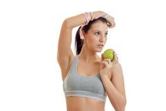 Graues Spitzen des jungen Eignungsmädchens oben angehoben ihrer Hand und hält die grüne Apple-Nahaufnahme Stockfoto