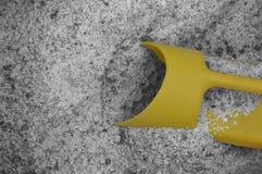 Graues Streusalz mit einer hellen gelben Schaufel Lizenzfreie Stockbilder