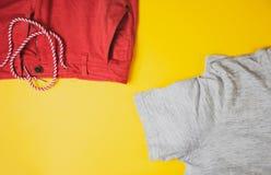 Graues T-Shirt und rote kurze Hosen auf gelbem Hintergrund, Ansicht von der Spitze stockbild