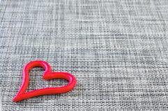 Graugewebe-Valentinsgrußhintergrund mit rotem Herzen auf ihm lizenzfreies stockfoto