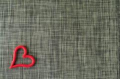 Graugewebe-Valentinsgrußhintergrund mit rotem Herzen auf ihm stockfotografie