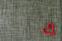 Graugewebe-Valentinsgrußhintergrund mit rotem Herzen auf ihm stockbilder