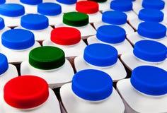 Graus das capacidades com várias cores das tampas com os produtos da leiteria e do ácido-leite Foto de Stock Royalty Free