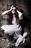 Grausigkeitsart geschossen: merkwürdiges verrücktes Mädchen und ihre moppet Puppe stockbild