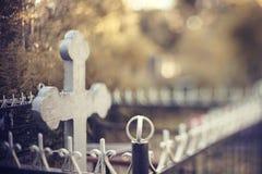 Grav med ett kors bak en fäktning arkivfoto
