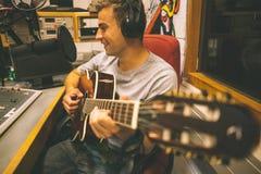 Gravação e jogo consideráveis de sorriso do cantor da guitarra fotos de stock