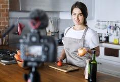 Gravação fêmea do blogger que cozinha a transmissão relativa em casa imagem de stock royalty free
