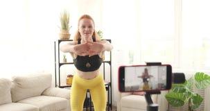 A gravação fêmea do vlogger um vídeo aquece aproximadamente exercícios video estoque