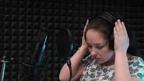 Gravação vocal do estúdio A mulher põe sobre fones de ouvido antes de cantar no estúdio da música video estoque
