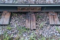 Grava con la hierba Los durmientes viejos, en ciudad allí son una línea de la tranvía En naturaleza, un tablero de madera mojado  fotografía de archivo libre de regalías