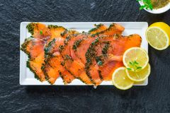 Gravadlax - Nordic dish of thinly sliced raw salmon cured in salt, sugar and dill. And accompanied by dill and mustard sauce - top view stock images
