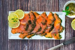 Gravadlax - Nordic dish of thinly sliced raw salmon cured in salt, sugar and dill. And accompanied by dill and mustard sauce - top view stock photo