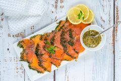 Gravadlax - Nordic dish of thinly sliced raw salmon cured in salt, sugar and dill. And accompanied by dill and mustard sauce - top view royalty free stock photos