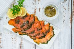 Gravadlax - Nordic dish of thinly sliced raw salmon cured in salt, sugar and dill. And accompanied by dill and mustard sauce - top view royalty free stock images