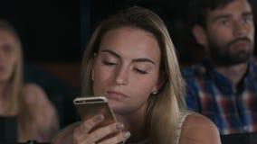 Gravado de um texting fêmea novo bonito durante filmes no cinema local fotos de stock royalty free