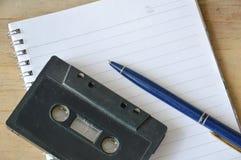 Gravador da cassete áudio e pena azul no livro Fotos de Stock