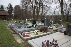 Gravar, gravstenar och kors på traditionell kyrkogård Votive stearinljus lykta och blommor på gravvalvstenar i kyrkogård Arkivfoton