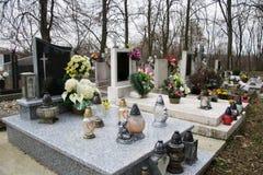 Gravar, gravstenar och kors på traditionell kyrkogård Votive stearinljus lykta och blommor på gravvalvstenar i kyrkogård Royaltyfri Foto