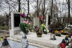Gravar, gravstenar och kors på traditionell kyrkogård Votive stearinljus lykta och blommor på gravvalvstenar i kyrkogård Royaltyfri Bild