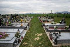 Gravar, gravstenar och kors på traditionell kyrkogård Votive stearinljus lykta och blommor på gravvalvstenar i kyrkogård Arkivbild