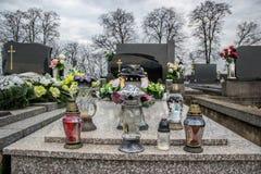 Gravar, gravstenar och kors på traditionell kyrkogård Votive stearinljus lykta och blommor på gravvalvstenar i kyrkogård Royaltyfria Bilder