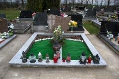 Gravar, gravstenar och kors på traditionell kyrkogård Votive stearinljus lykta och blommor på gravvalvstenar i kyrkogård Fotografering för Bildbyråer