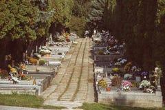 Gravar, gravstenar och kors på traditionell slovakisk kyrkogård Votive stearinljus lykta och blommor på gravvalvstenar i kyrkogår Royaltyfria Foton