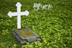 Grave. Old tombstone with white wooden cross surrounded by green plants Stock Photo