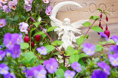 Grave angel between flowers by grave stones Royalty Free Stock Images