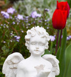 Grave angel. In front of tulips in spring stock photography