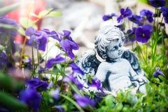 Grave angel between horned violets. Grave angel, angel between horned violets Royalty Free Stock Image