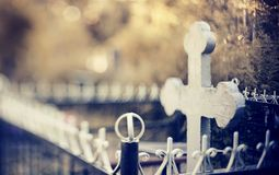 Grave with a cross behind a fencing. Royalty Free Stock Image
