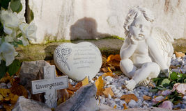 Grave with cross, heart and angels and german text Stock Image