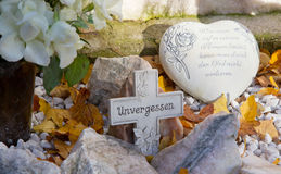 Grave with cross and heart and german text. Modern grave jewelry with cross and heart Royalty Free Stock Photo