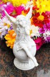 Grave decoration in autumn. An angel sitting in front of flowers royalty free stock images