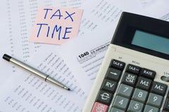 Grave el tiempo escrito en nota rosada de la etiqueta engomada con sobre U S Forma de impuesto detallada de las deducciones Imágenes de archivo libres de regalías