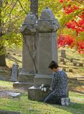 Grave flowers. Woman putting silk roses on cemetery headstone Royalty Free Stock Photo