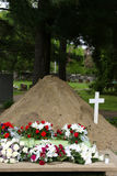Grave with flowers and cross royalty free stock photo